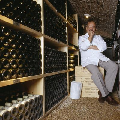 """Chef Pierre Troisgros sitting in the wine cellar of his restaurant """"Troisgros"""" in Roanne which has had 3 Michelin stars awarded to it since 1968. (Photo by Eric Préau/Sygma via Getty Images)"""